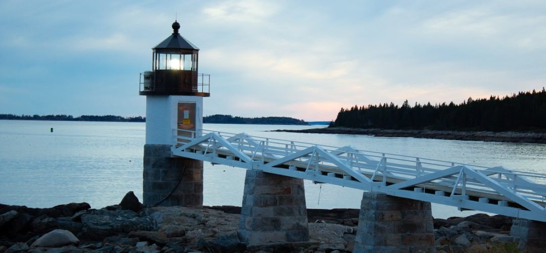 lighthouse near waterscape on top of some rocks